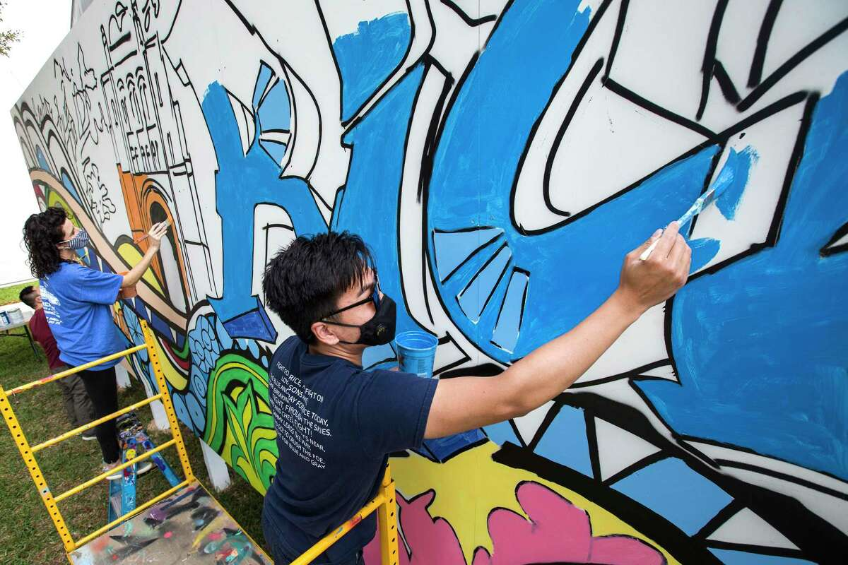 Student volunteers Frances Gallego, left, and Jefferson Ren help work on a mural, designed by graffiti artist Gonzo247, on the side of one of the temporary classrooms on the campus at Rice University Monday, Oct. 26, 2020 in Houston. The mural was commissioned as part of Rice's