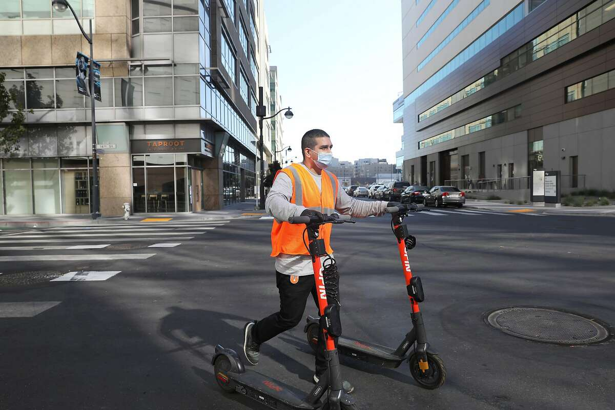 Michael Delgado, SPIN operations specialist, walks scooters down 16th street to a rack while deploying scooters at Chase Center on Monday, October 19, 2020 in San Francisco, Calif.