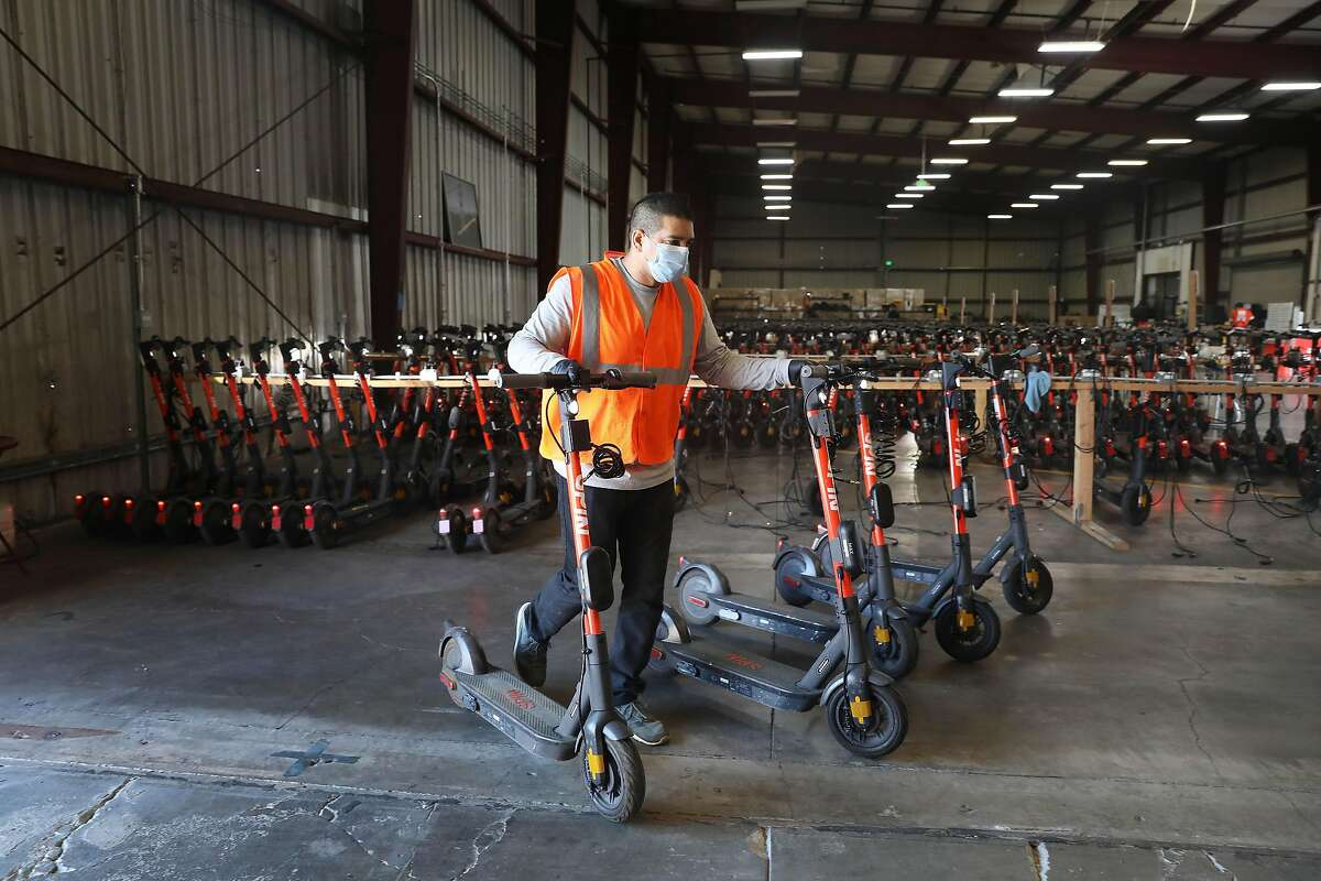 Michael Delgado, SPIN operations specialist, loads a van with SPIN scooters at a San Francisco warehouse before deploying them on Monday, October 19, 2020 in San Francisco, Calif.