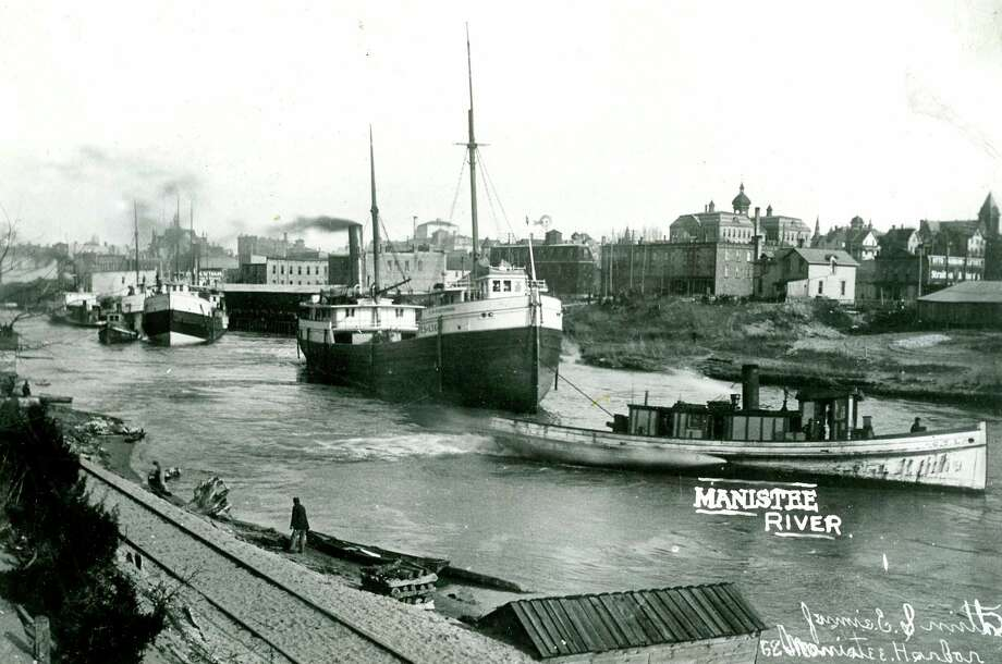 Tugboats tow lake vessels out of the Manistee River Channel. (Manistee County Historical Museum photo)