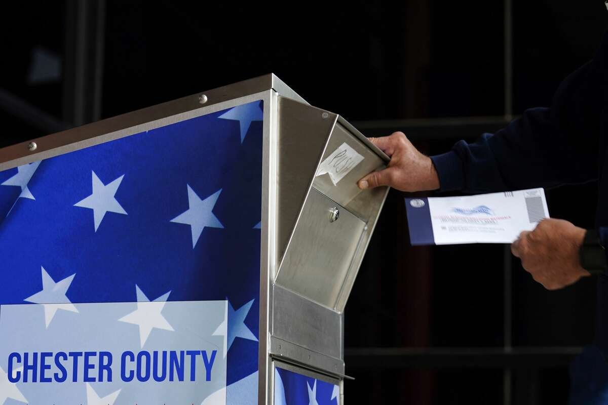 A man drops off his ballot for the 2020 General Election in the United States outside the Chester County Government Services Center, Friday, Oct. 23, 2020, in West Chester, Pa.