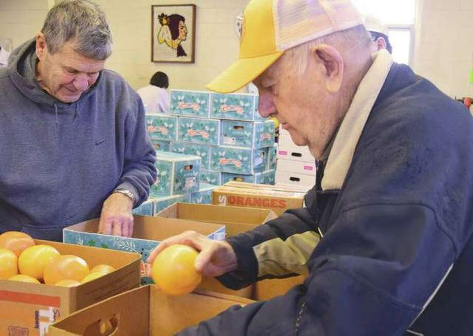 Gary Reif (left) and Jim Barber inspect fruit in December before filling orders for the Lions Club's annual fruit sale. Photo: Journal-Courier