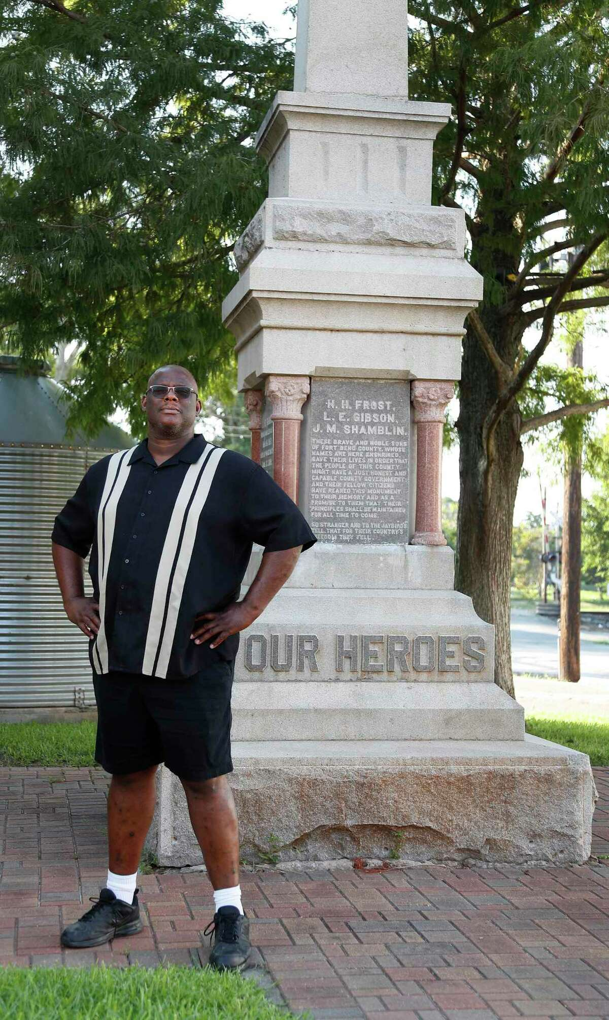 Tres Davis, a Richmond resident, stands next to a controversial monument that honors white supremacists on August 6, 2020, in Richmond. Over the summer, community members asked for the monument to be removed and Davis sought to claim ownership to do so. Fort Bend County commissioners voted unanimously on Oct. 27, 2020 to enter into an agreement with the city of Richmond to move the controversial monument to a local cemetery.
