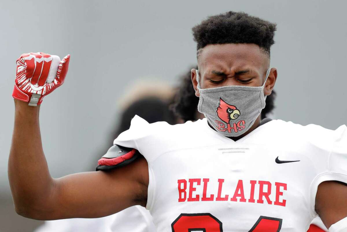 Bellaire defensive back Lorel Fotso (24) closes his eyes as he raises his fist while the national anthem plays before a District 18-6A high school football game at Delmar Stadium, Saturday, Oct. 24, 2020, in Houston.