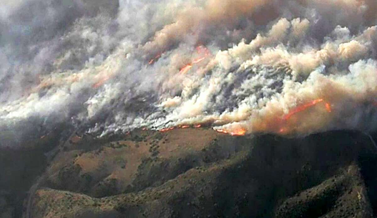 This photo from video provided by KNBC-TV shows smoke and flames from the Silverado fire that is threatening areas near Irvine in Southern California's Orange County Monday, Oct. 26, 2020. Driven by strong, gusting winds, the fire grew rapidly Mondy morning. Although winds will carry smoke from the Creek Fire and other wildfires along the Sierra crest, air quality is expected to remain good throughout most of the Bay Area.