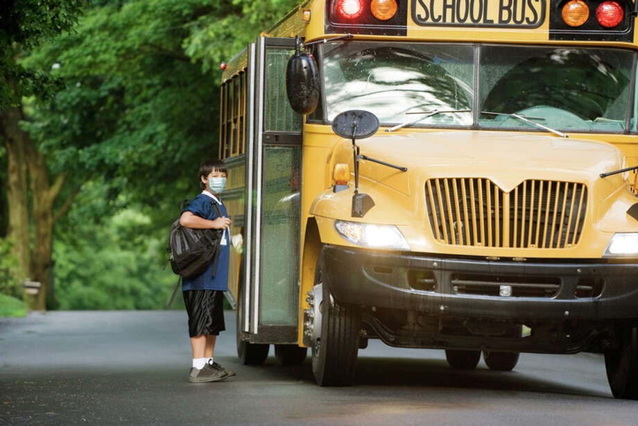 School bus picking up elementary student wearing surgical mask boarding at bus stop. Photo: Nycshooter/Getty Images