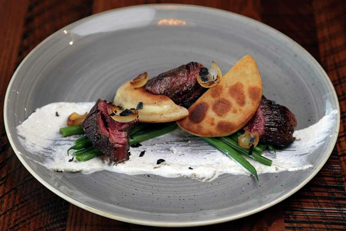 Hanger steak, potato and cheddar pierogi, and horseradish cream at Riel restaurant.