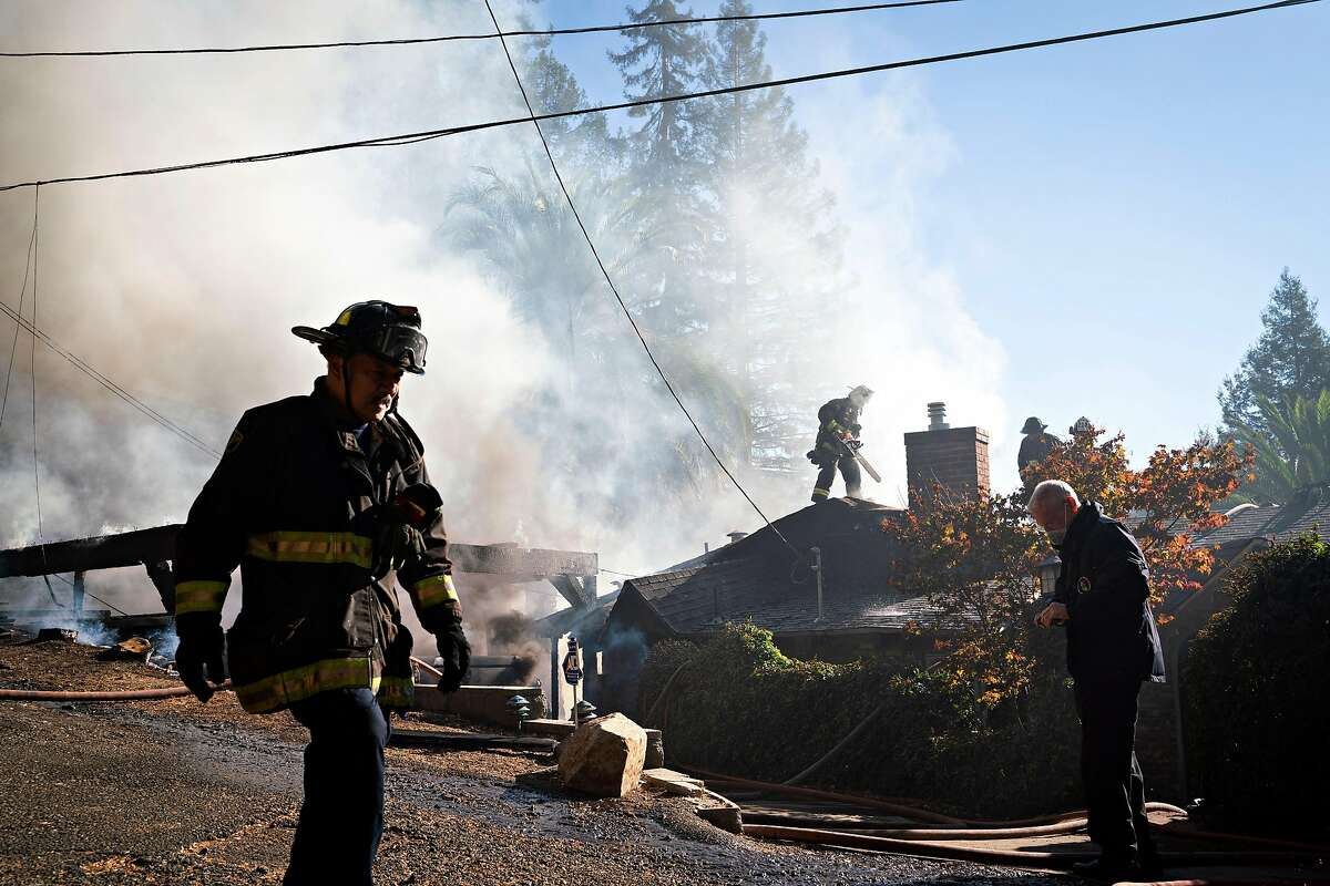 Firefighters battle a two-structure fire on Crown Avenue in Oakland on Tuesday.