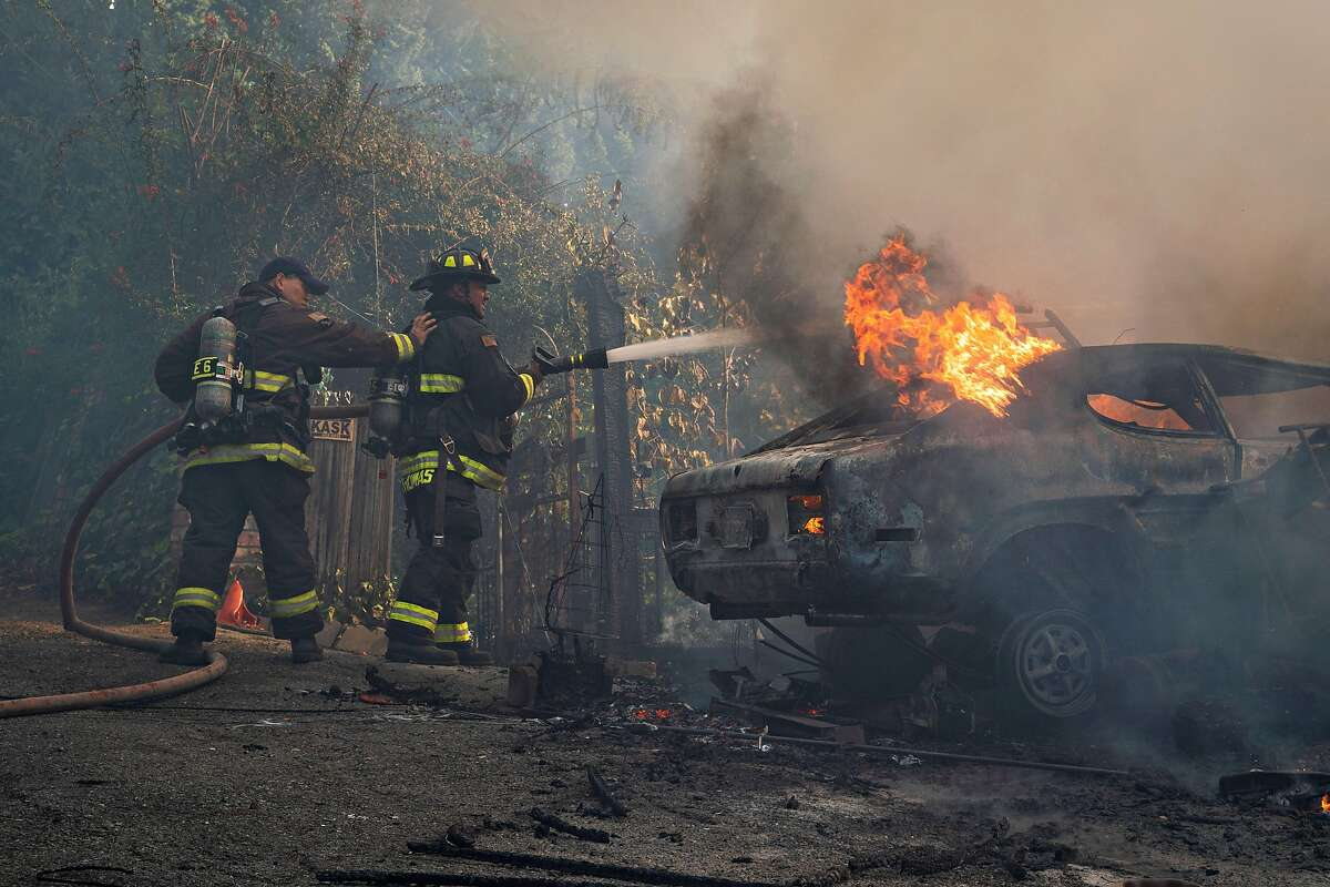 Firefighters extinguish flames engulfing a car during a structure fire on Crown Avenue in Oakland on Tuesday.