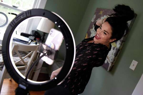 TikTok star Samantha Ramsdell records a video on her phone at her home in Stamford, Conn. Tuesday, Oct. 27, 2020. Ramsdell has amassed more than 500,000 followers on TikTok under the user name @samramsdell5 since pivoting to the mobile video app early in the pandemic.
