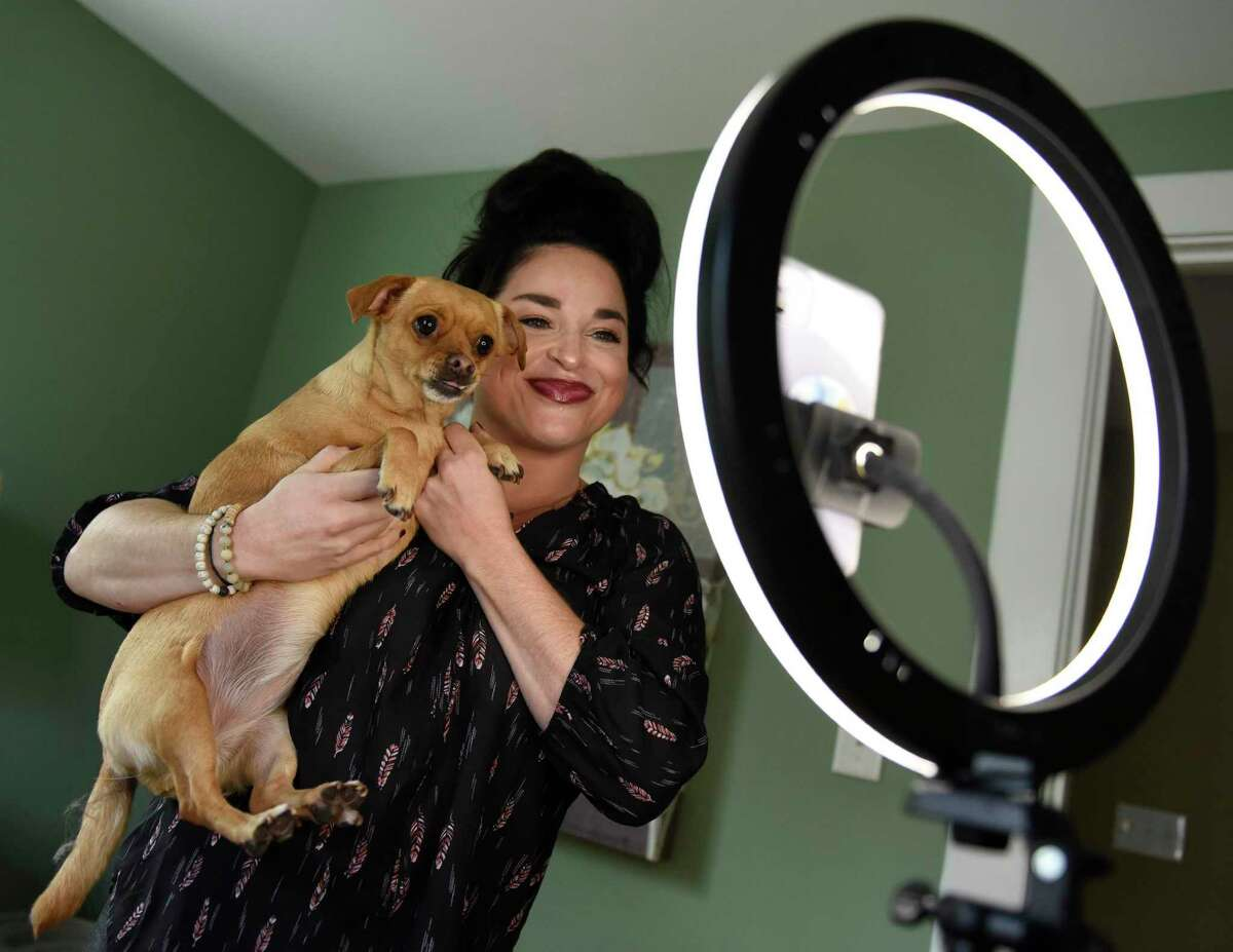 TikTok star Samantha Ramsdell records a video with her dog, Prudence, on her phone at her home in Stamford, Conn. Tuesday, Oct. 27, 2020. Ramsdell has amassed more than 500,000 followers on TikTok under the user name @samramsdell5 since pivoting to the mobile video app early in the pandemic.