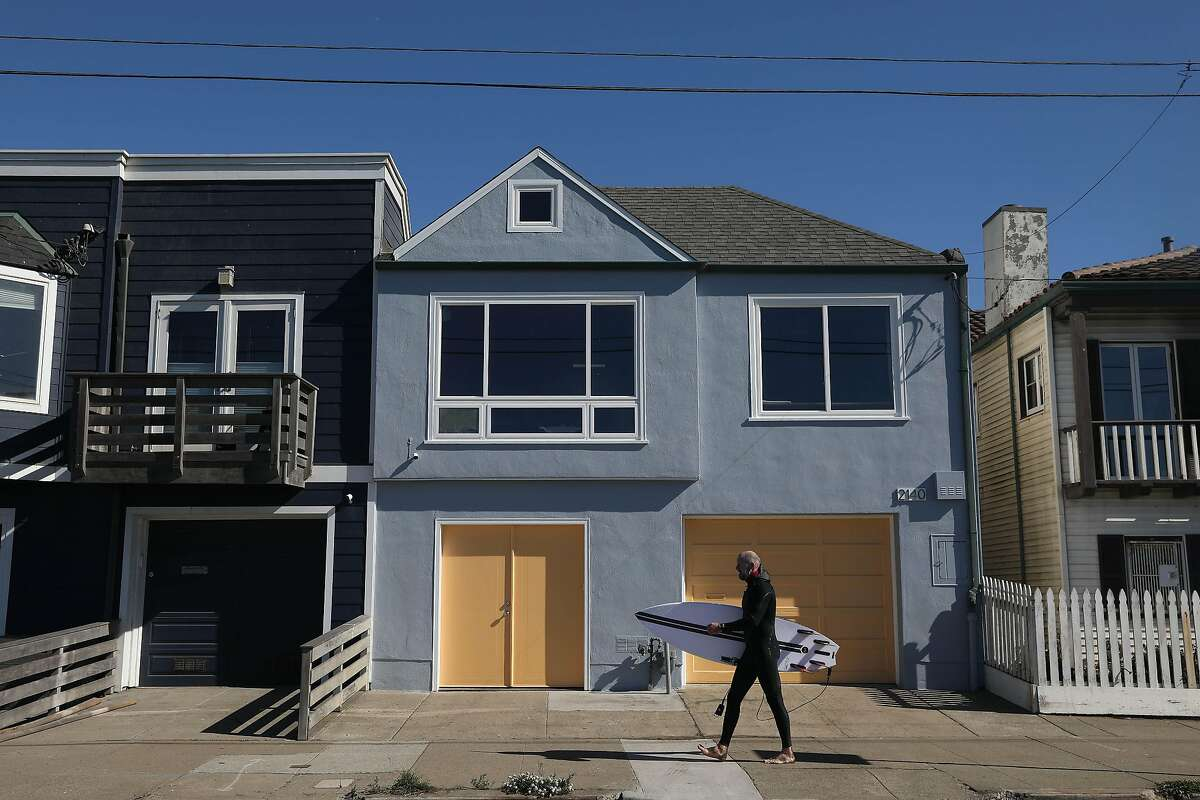 Scott Tusher of Mill Valley, carries a surfboard as he walks past a house on the lower Great Highway which used to look like a painting by artist Pier Mondrian and now has a new look on Tuesday, October 27, 2020 in San Francisco, Calif.