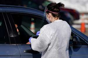 A tester administers a swab test at a drive-in COVID-19 testing site Tuesday, Oct. 27, 2020, in Federal Heights, Colo. Denver will enforce tighter restrictions for restaurants, retail and offices, reducing maximum capacity from 50 percent to 25 percent amid a spiraling rise in cases of the coronavirus in the state in the past month. (AP Photo/David Zalubowski)