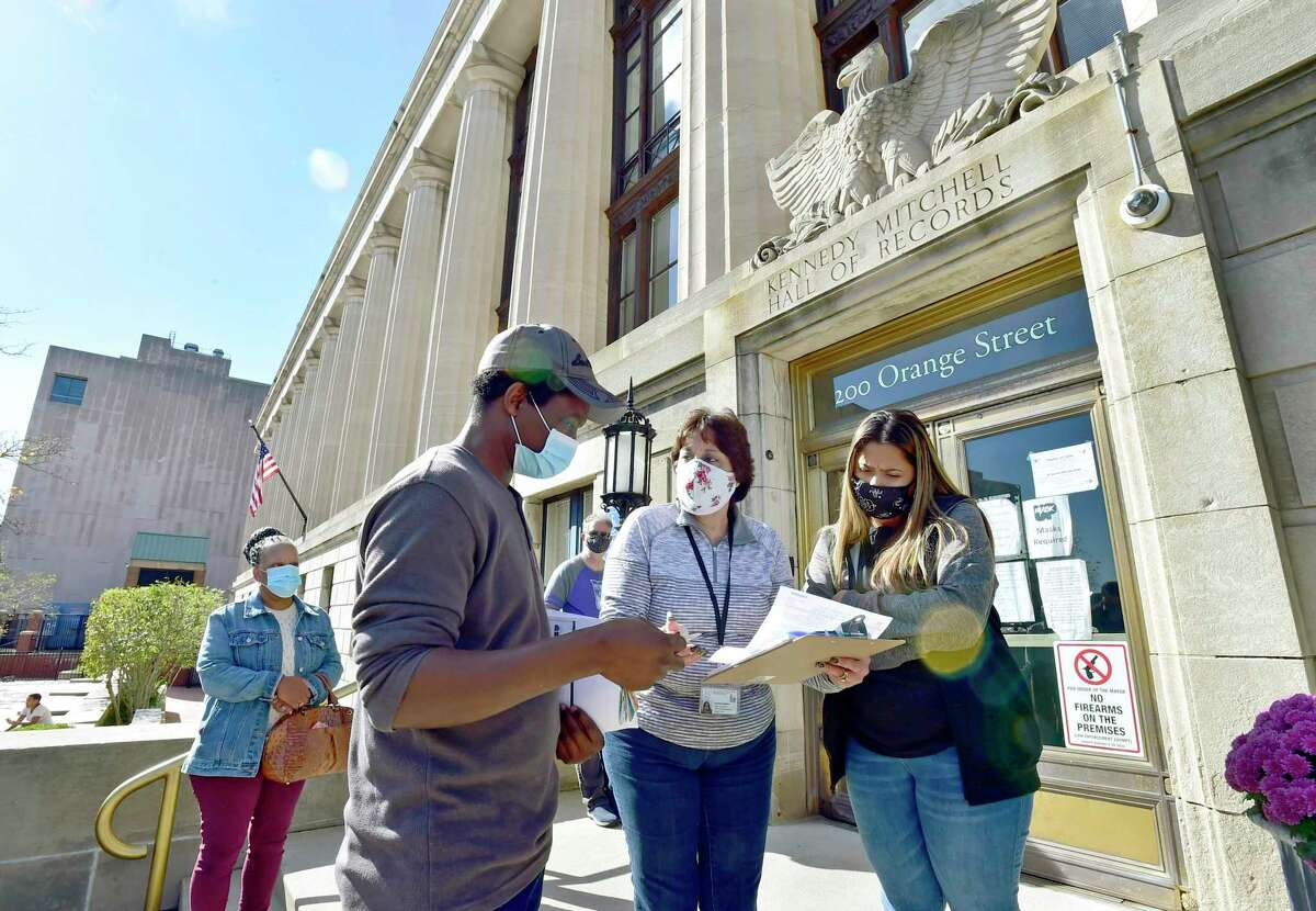Liz DeMatteo, second from right, City of New Haven Democratic Deputy Registrar of Voters Oct. 27, 2020 in front of the Hall of Records in New Haven helps a potential voter, second from left, as voters wait to register to vote or get their absentee ballots.