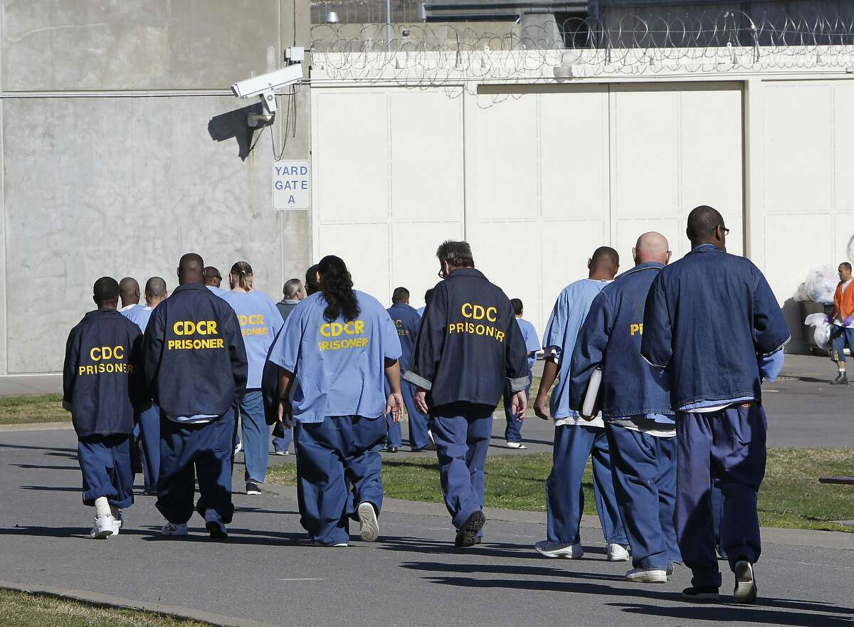 FILE - In this Feb. 26, 2013, file photo, inmates walk through the exercise yard at California State Prison Sacramento, near Folsom, Calif. In November 2020, California voters will consider rolling back a host of criminal justice changes in what amounts to a referendum on whether the famously progressive state has become too lenient. Proposition 20 would amend criminal sentencing and supervision laws enacted during the administration of Gov. Jerry Brown that critics say are too favorable to criminals, while Proposition 25 could overturn a 2018 law that eliminates cash bail. (AP Photo/Rich Pedroncelli, File)