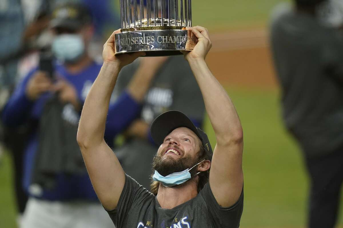 Los Angeles Dodgers pitcher Clayton Kershaw celebrates with the trophy after defeating the Tampa Bay Rays 3-1 to win the baseball World Series in Game 6 Tuesday, Oct. 27, 2020, in Arlington, Texas. (AP Photo/Eric Gay)