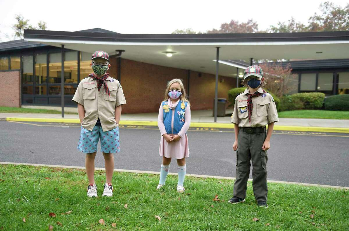 Fifth-grader Paul Anthony Cappiali, left, second-grader Katie Cappiali, center, and fifth-grader Jack Wade pose outside North Street School in Greenwich, Conn. Tuesday, Oct. 20, 2020. The trio are among the Girl Scouts and Boy Scouts that packed and distributed 350 Halloween candy bags for underserved clients of Community Centers Inc. The annual Community Centers Halloween party was canceled this year due to COVID-19 precautions, so CCI leaders reached out to local Girl Scout and Boy Scout troops to pack candy bags for children who would have been in attendance.