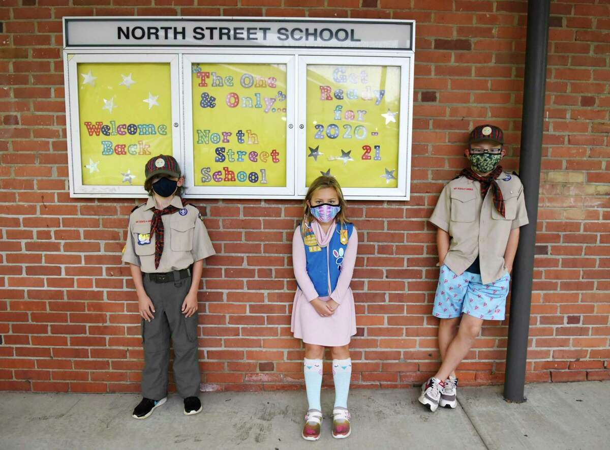 Fifth-grader Jack Wade, left, second-grader Katie Cappiali, center, and fifth-grader Paul Anthony Cappiali pose outside North Street School in Greenwich, Conn. Tuesday, Oct. 20, 2020. The trio are among the Girl Scouts and Boy Scouts that packed and distributed 350 Halloween candy bags for underserved clients of Community Centers Inc. The annual Community Centers Halloween party was canceled this year due to COVID-19 precautions, so CCI leaders reached out to local Girl Scout and Boy Scout troops to pack candy bags for children who would have been in attendance.