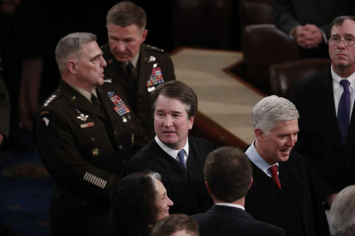 Neil Gorsuch, associate justice of the U.S. Supreme Court, right, and Brett Kavanaugh, associate justice of the U.S. Supreme Court, center, arrive ahead of a State of the Union address at the U.S. Capitol in Washington on Feb. 4, 2020.