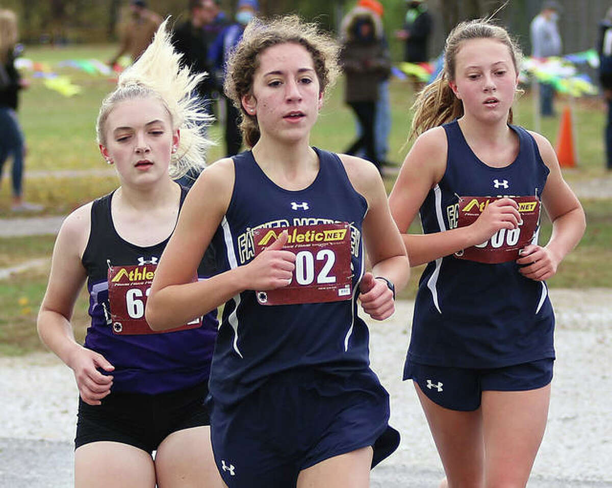 Father McGivney's Emma Martinez, front, and Claire Stanhaus, right, work together to pass a runner during the Class 1A Carlinville Regional on Saturday.