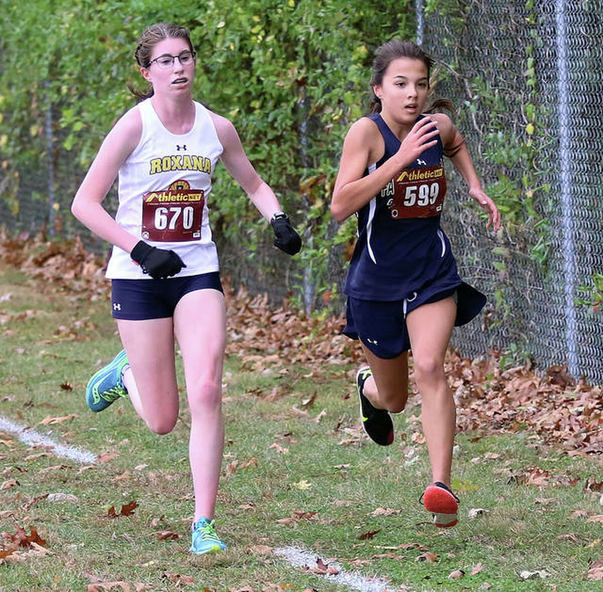 Father McGivney's Kaitlyn Hatley, right, attempts to pass Roxana's Riley Doyle in the closing meters of the Class 1A Carlinville Regional.