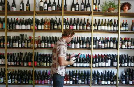 Light Years co-owner Steve Buechner looks through the stock in his hybrid shop-bar devoted to natrual wine.