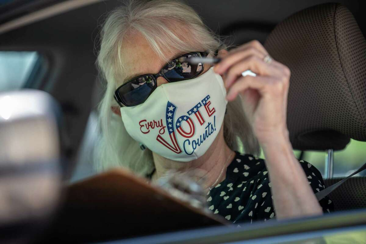A voter wearing a protective mask that reads