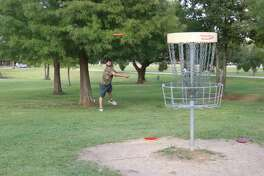 League City resident Jordan Richards' approach shot is on the mark at Taylor Lake Village Disc Golf Course.