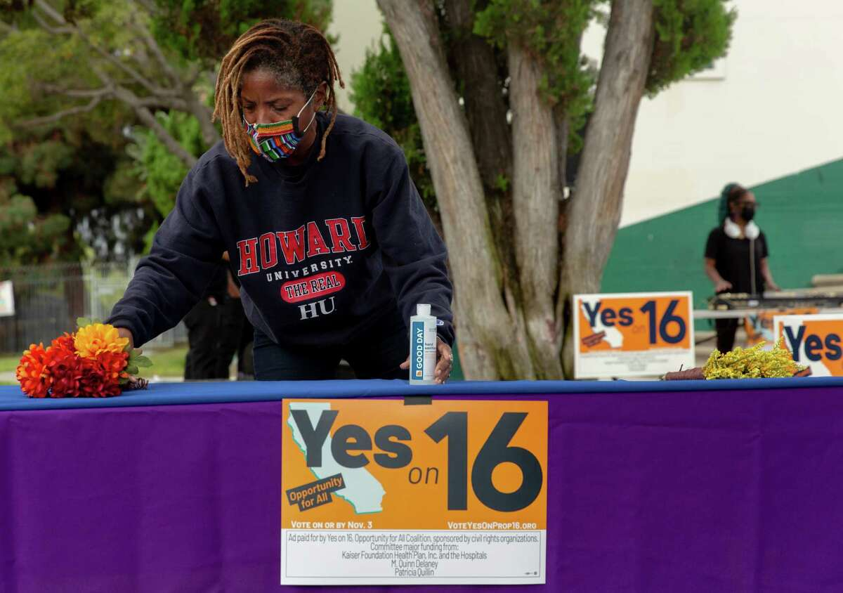 Apryl Sims sets up a table at a Proposition 16 rally at Dorsey High School in Los Angeles during early voting in California. Passage of Proposition 16 would enable California state and local entities to consider race, sex, color, ethnicity and national origin in public education, public employment and public contracting.