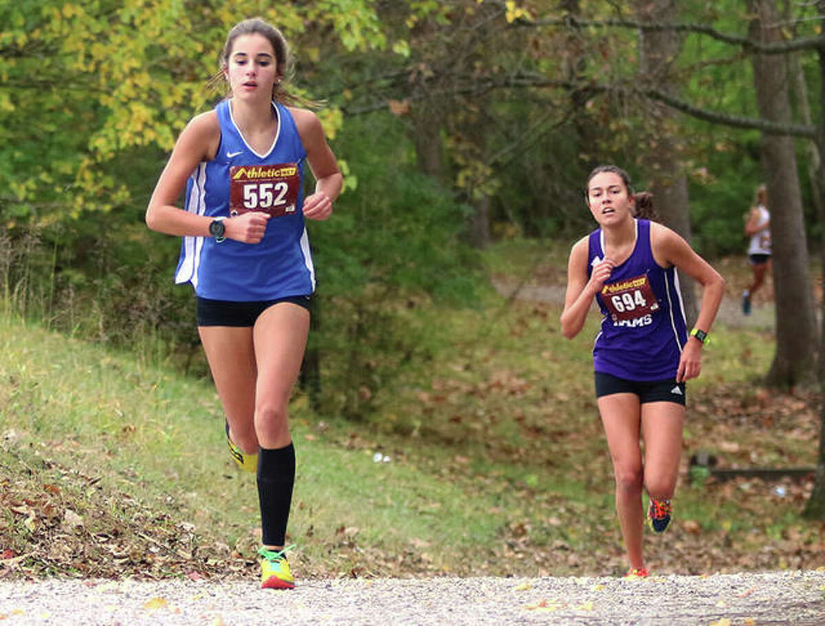 Marquette Catholic sophomore Kailey Vickrey (left) leads Shelbyville sophomore Ellie Nohren up the hill and out of the woods in the final mile of the Carlinville Class 1A Regional on Saturday at Loveless Park in Carlinville. Vickrey finished fourth in a race in a personal-best time, with Nohren placing fifth.