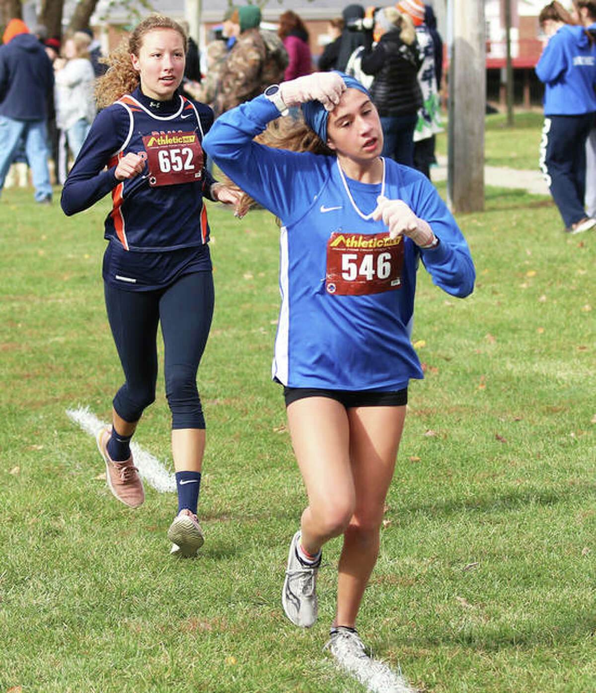 Marquette Catholic's Kate Johnson (front) sheds her headband as her heat warms up in the Carlinville Class 1A Regional at Loveless Park. Johnson was one of six Explorers to set a PR in the race.