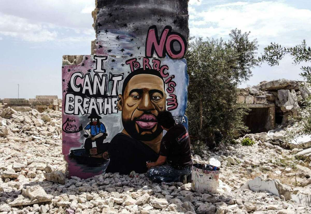 Thirty-six-year-old graffiti artist Aziz Asmar paints a mural depicting of George Floyd on a wall of house ruins in the Binnish district in Idlib province, Syria, on June 2, 2020.