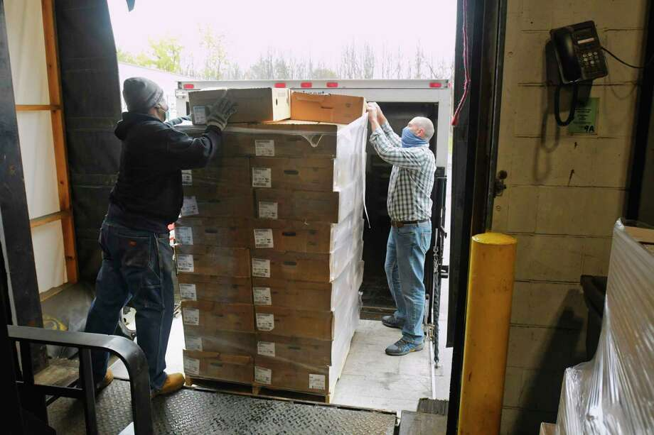 """Chris Thomas, left, forklift operator at the Regional Food Bank of Northeastern New York, and Tom Schofield, SICM pantry manager in Schenectady, load boxes of frozen turkeys onto a truck at the Regional Food Bank on Wednesday, Oct. 28, 2020, in Latham, N.Y. Trustco Bank donated 2,000 turkeys that will be distributed to food pantries throughout the area. Mark Quandt, executive director of the Regional Food Bank, said that food distribution out of the Regional Food Bank has been up 42% over the last seven months. """"This donation is a tremendous help to families we serve and it's the largest donation of turkeys we have received in over 40 years"""", Quandt said.   (Paul Buckowski/Times Union) Photo: Paul Buckowski, Albany Times Union / (Paul Buckowski/Times Union)"""