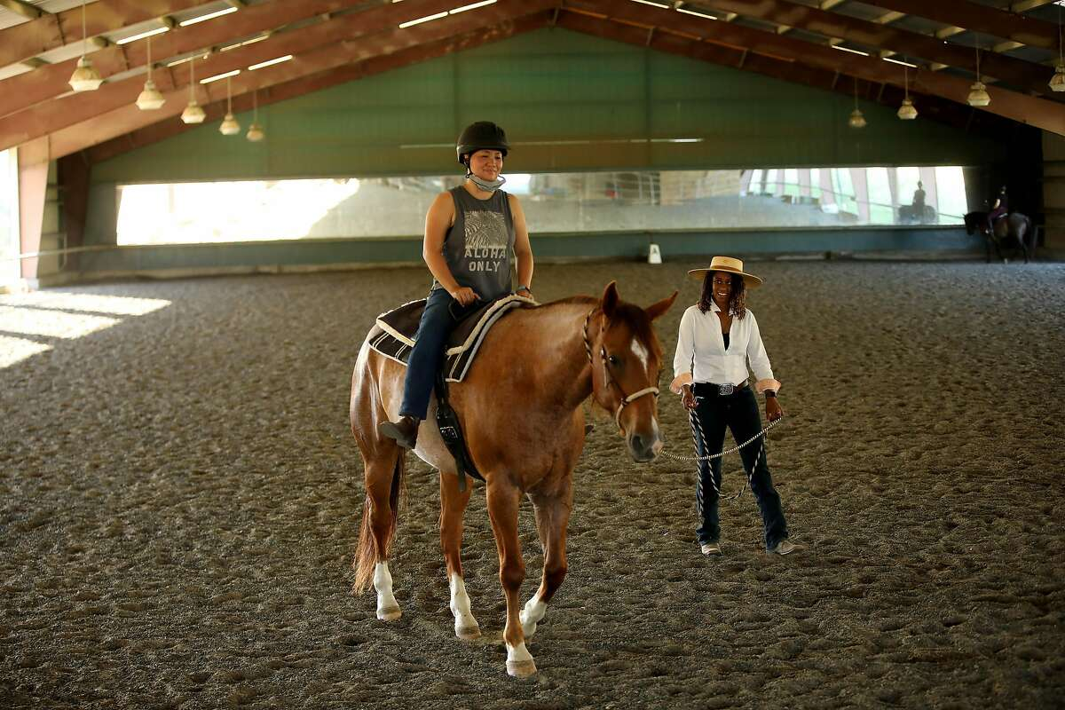 Brianna Noble instructs student Jennifer Lee, of Oakland, as she rides on Dapper Dan during a lesson at Hossmoor in Briones, Calif., on Wednesday, June 3, 2020. Noble, who works at the stables, rode her horse, Dapper Dan, with a Black Lives Matter sign on the back through the early evening crowds before the George Floyd protests Friday in downtown Oakland. The photos of Floyd have been much shared on social media as a hopeful message during the protests.