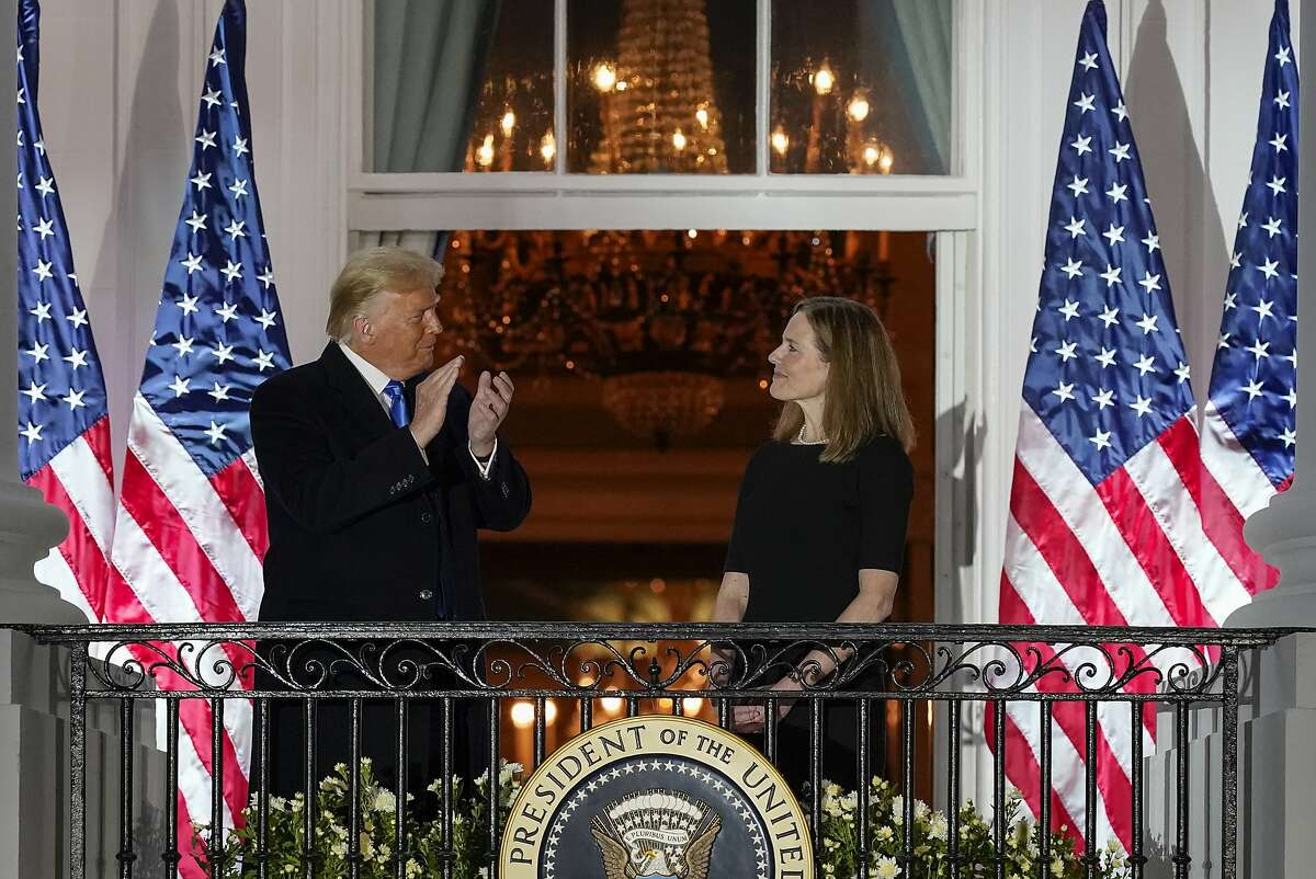 President Trump and Amy Coney Barrett stand on the Blue Room Balcony after Supreme Court Justice Clarence Thomas administered the Constitutional Oath to her on the South Lawn of the White House White House in Washington on Oct. 26.