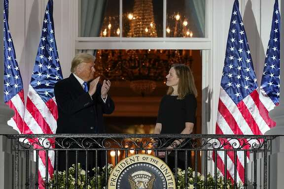 President Donald Trump and Amy Coney Barrett stand on the Blue Room Balcony after Supreme Court Justice Clarence Thomas administered the Constitutional Oath to her on the South Lawn of the White House White House in Washington, Monday, Oct. 26, 2020. Barrett was confirmed to be a Supreme Court justice by the Senate earlier in the evening. (AP Photo/Alex Brandon)