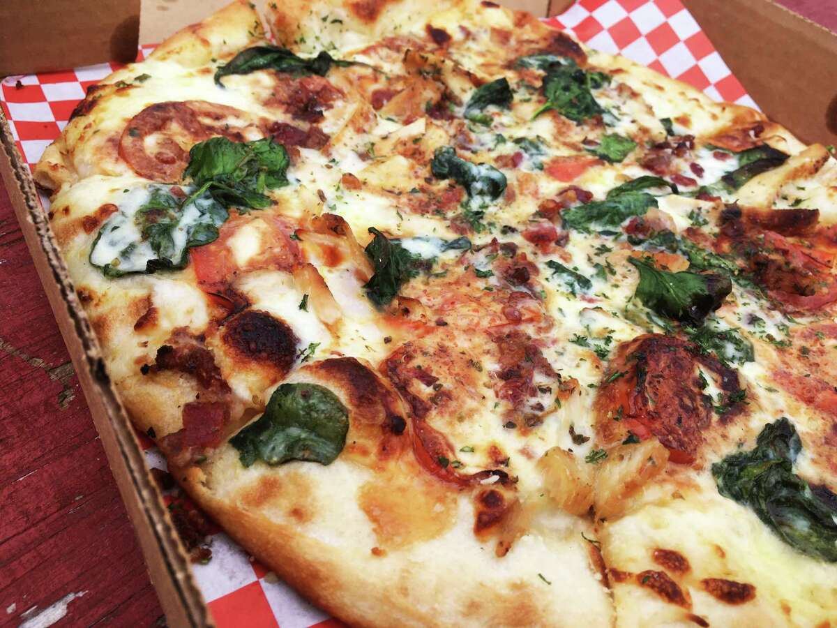 The Alfredo Pizza at Cosa Nostra Pizzeria is carried with the sauce and garlic.