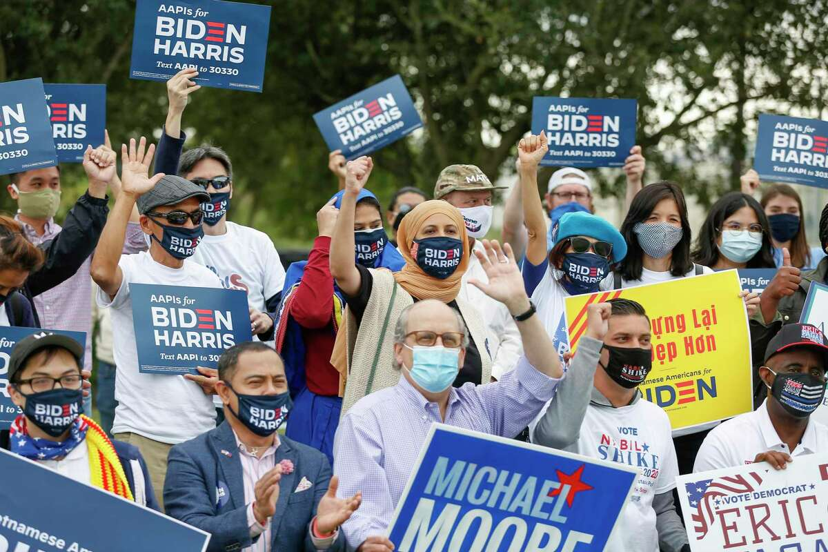 While having a group photo taken, attendees cheer at a Pan Asian rally for Biden at the Southern News Group Saturday, Oct. 24, 2020, in Houston.