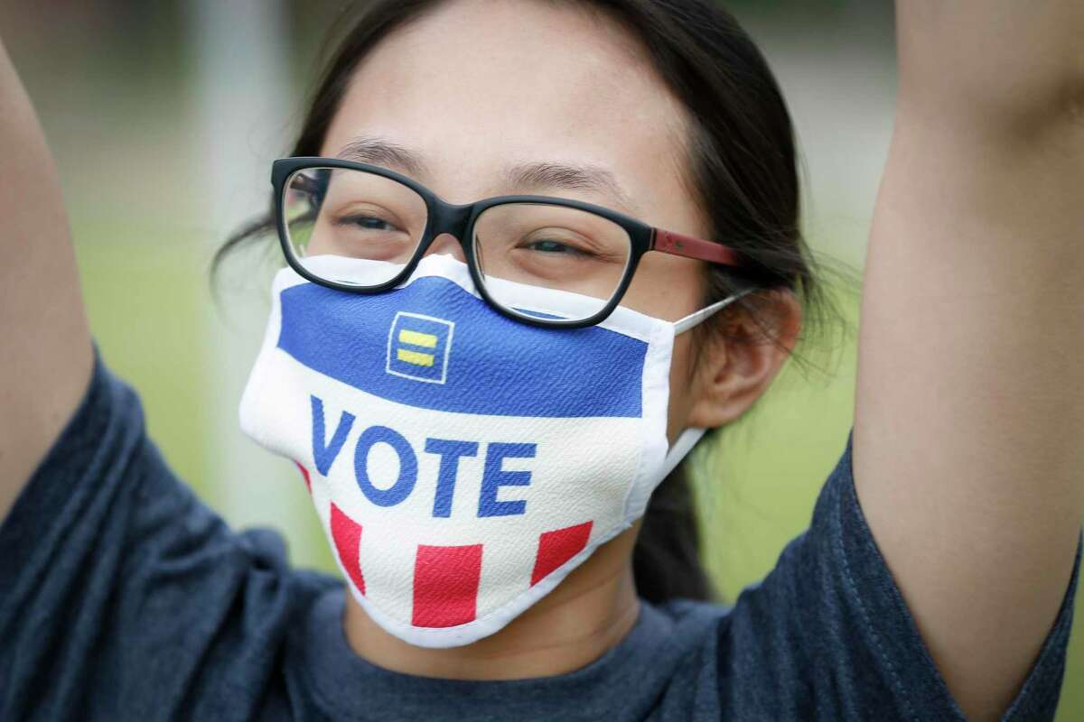 Thu-Mai Nguyen cheers as she wears a mask during a Pan Asian rally for Biden at the Southern News Group Saturday, Oct. 24, 2020, in Houston.