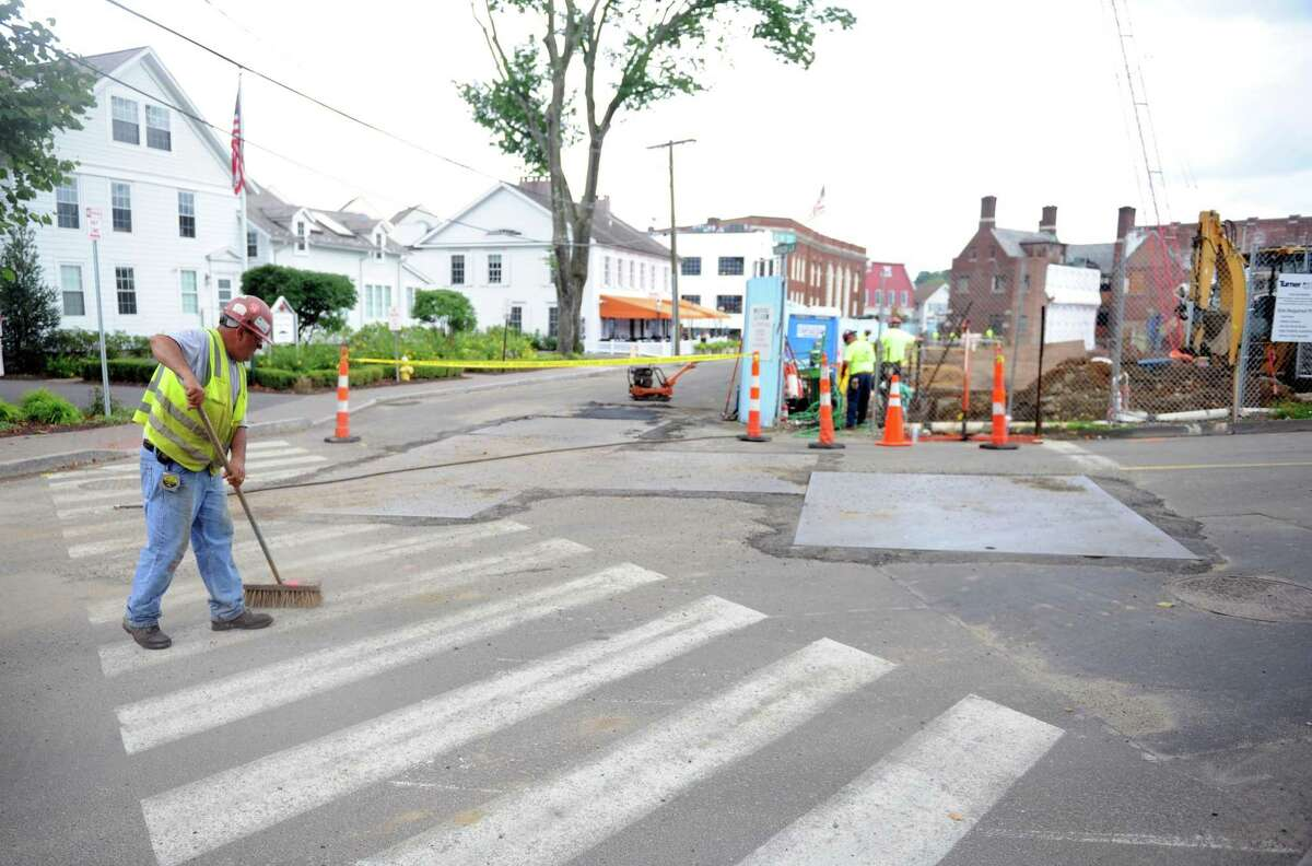 A worker sweeps debris from Church Lane during construction Wednesday, July 15, 2015 at the Bedford Square development on property bordered by Post Road East, Main and Elm streets in Westport.