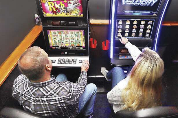 Two gamblers try their luck on the slot machines inside Bubby and Sissy's bar on Belle Street in Alton. The Glen Carbon Board of Trustees voted to pass an ordinance to allow video gaming Tuesday, allowing video gaming systems similar to these in specific establishments.