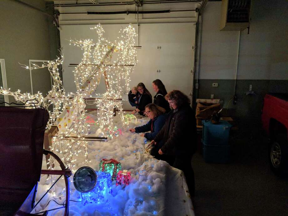 Gladwin County Festival of Lights Christmas Parade Committee members, from right, Lori Stout, Kim Bruner, Selena Volmering and Wanda McClain (holding then 1-year-old son Andrew) along with, not pictured, Shannon Smith-Dorn, putting the finishing touches on their 2019 Santa float. While there won't be an actual parade this year, there will still be plenty of floats to see. Richardson Chevrolet Gladwin donated space for the group to work on the parade last year. The tree lighting is at 5:30 p.m. and the float viewing begins afterwards along Main Street. (Photo by Tereasa Nims for the Daily News)