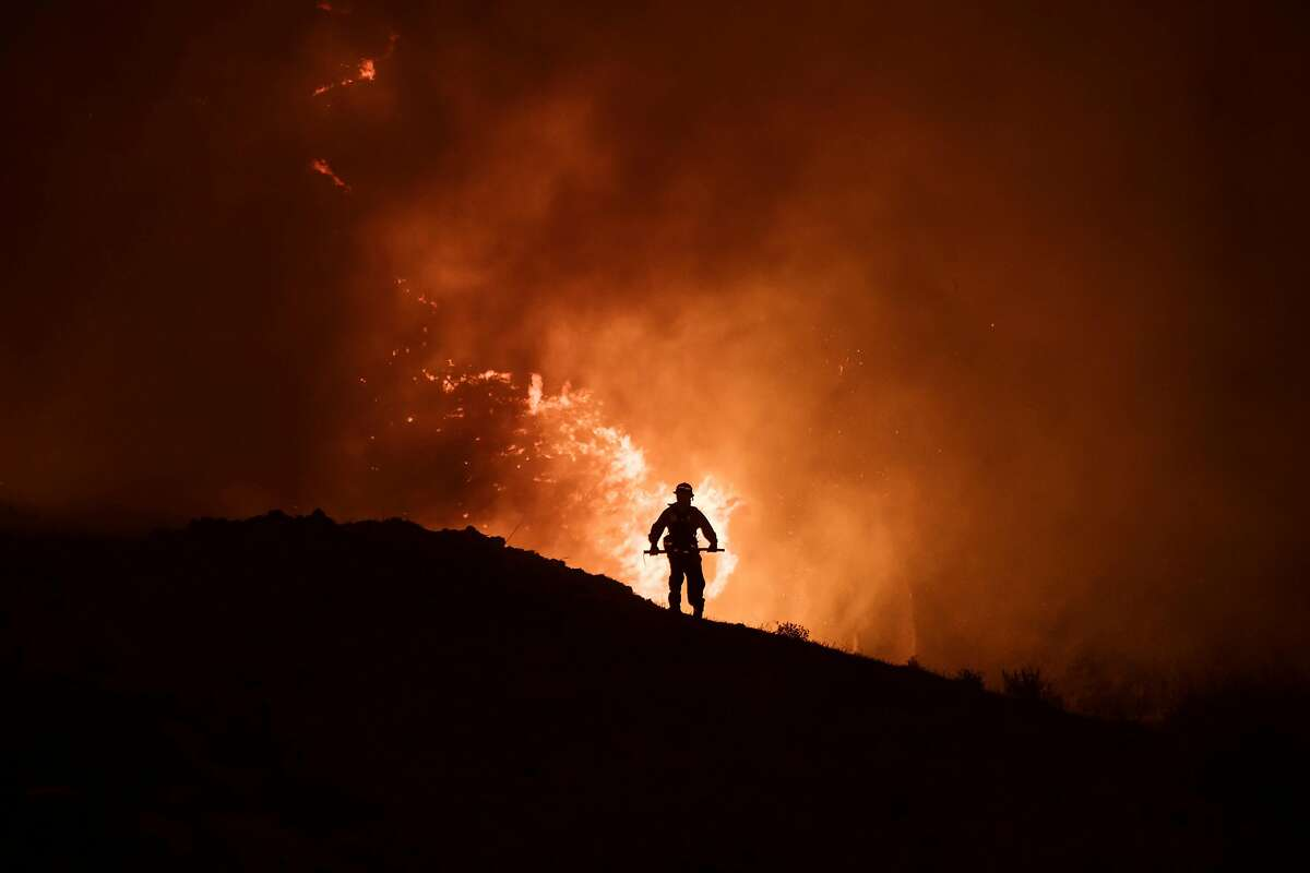 A firefighter fights the Blue Ridge Fire in Chino Hills, Calif., on Oct. 27, 2020. The Silverado Fire and the Blue Ridge Fire nearly doubled in size overnight, and have forced more evacuations in Irvine and other parts of Orange County.