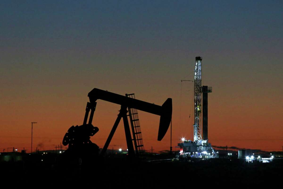 FILE - This Oct. 9, 2018, file photo shows an oil rig and pump jack in Midland, Texas. The Environmental Integrity Project noted in a report released Thursday, May 9, 2019, that the Permian Basin, which include some West Texas cities, such as Midland, is one of the most productive hydrocarbon regions in the world. But the report says a consequence of that production is dangerous levels of sulfur dioxide escaping into the air around Odessa and other locations. (Jacob Ford/Odessa American via AP, File)