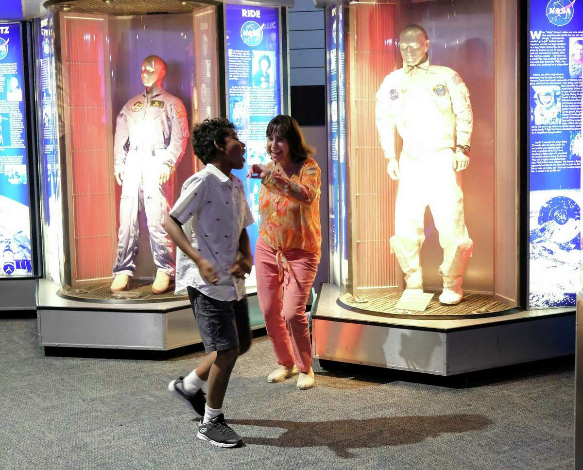 Annette Brown of Lakeway, Texas, dances with her grandson, Maddox, of Colorado Springs during a party celebrating Apollo Mission's splash down at Space Center Houston on Wednesday, July 24, 2019.
