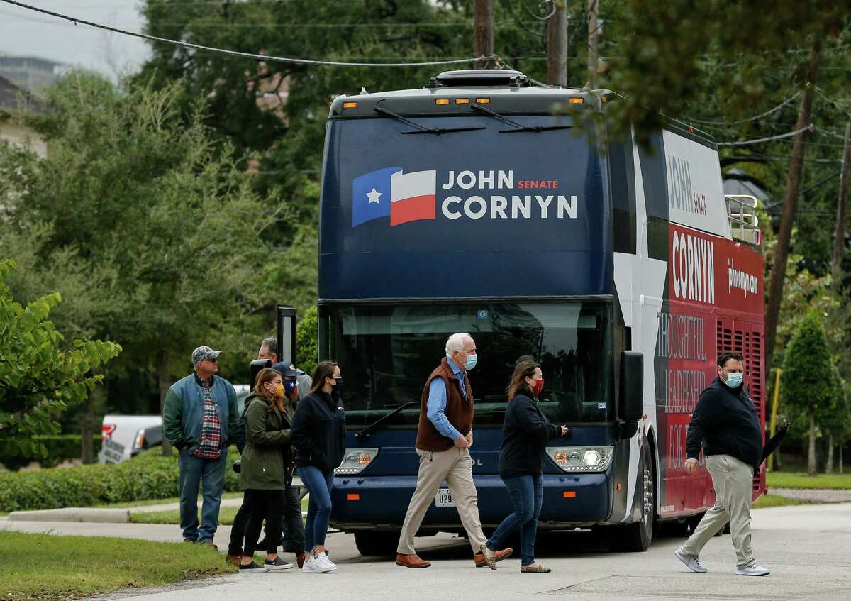 Sen. John Cornyn, center, gets off his Texas tour bus, while stopping at a