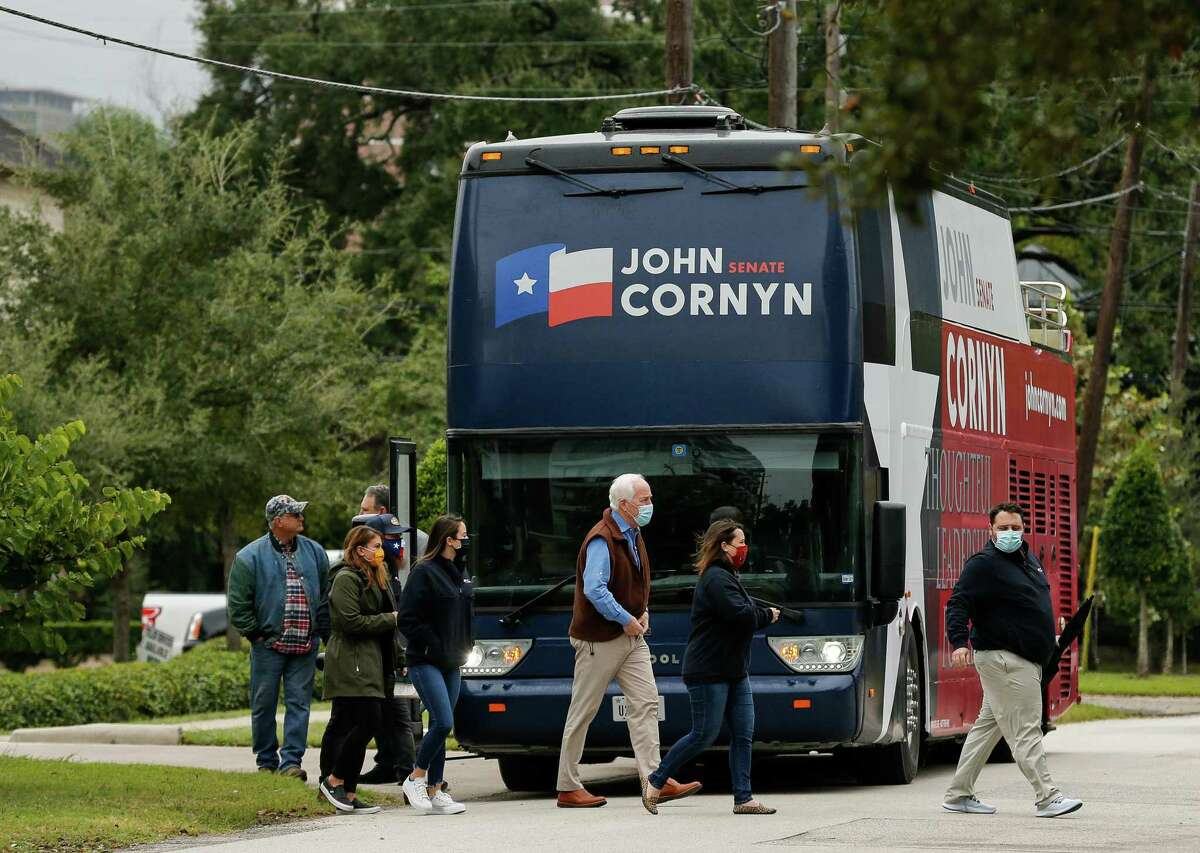 """Sen. John Cornyn, center, gets off his Texas tour bus, while stopping at a """"Back the Blue"""" event with Gov. Greg Abbott at the Houston Police Officer's Union Headquarters on Wednesday, Oct. 28, 2020, in Houston."""