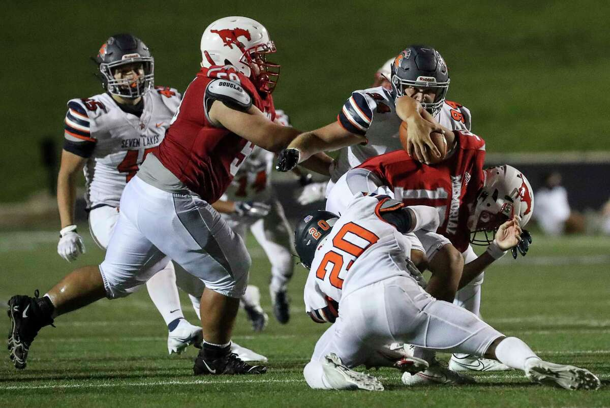 Memorial Mustangs Chase Goodwin (15) is tackled by Seven Lakes Spartans Adam North (20) during the fourth quarter of a football game Thursday, Sept. 24 2020, at Darrell Tully Stadium in Houston.
