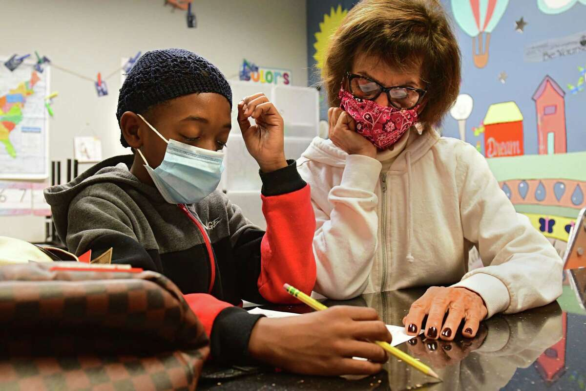 Aireon Myles of Albany, 10, gets help with his homework from tutor Sandra Olson in the homework room at the South End Children's Cafe on Wednesday, Oct. 28, 2020 in Albany, N.Y. (Lori Van Buren/Times Union)
