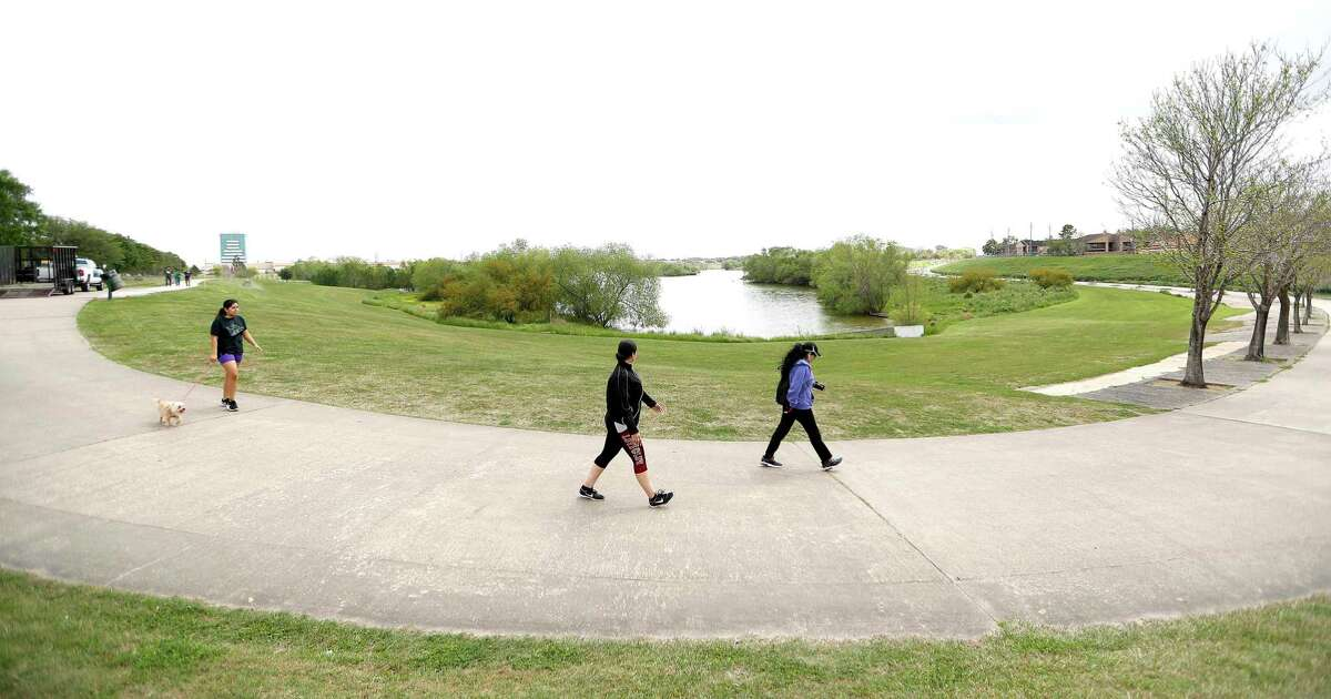 People walk along trails near Bellaire and the Sam Houston Tollway close to Brays Bayou, in Westchase on March 18, 2020. Westchase - about as suburban as you can get with apartment complexes, McMansions and office parks, is the only place where Buffalo Bayou and Brays Bayou actually connect by trail.